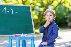 image of schoolboys  - Little preschool boy at blackboard practicing writing letters and mathematics outdoor school or nursery - JPG