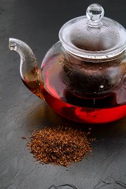 stock photo of fynbos  - Rooibos tea dry leaves and a small glass teapot brewing on black slate surface - JPG