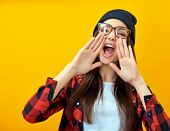 Hipster girl screaming like in megaphone holding hands near her face with open mouth. Young woman to poster