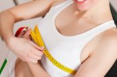 Thin woman measuring her chest with a tape measure, only the torso to be seen