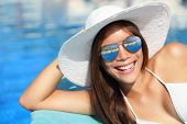 Summer bikini girl smiling by pool. Beautiful young woman wearing beach hat and sunglasses at tropical resort. Beautiful Asian Caucasian female model.