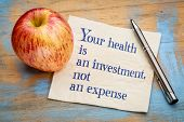 Your health is an investment, not an expense - wellness concept - handwriting on a napkin with a fre poster