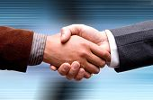 business handshake on technology background