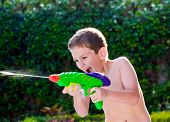 Kid Playing With Water Toys In Backyard.