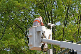 stock photo of traffic signal  - A man in a lift bucket installing a traffic camera on a traffic light - JPG