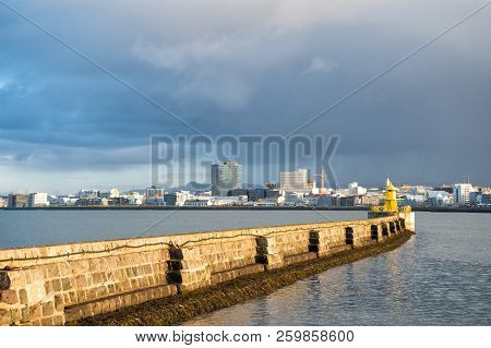 poster of Lighthouse On Sea Pier In Reykjavik Iceland. Lighthouse Yellow Bright Tower At Sea Shore. Seascape A