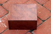 a hand made wooden box on red brick contains a Circa 1889, Model 95, Type II Model 3 Double Derringe
