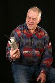 a man shows frustration while using a 1980s era cellular telephone also known as a