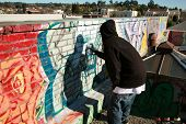 an unidentifiable person spray paints graffiti on