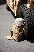 us military flack jacket and helmet lay against a h1 humvee