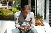 um rapaz negro quadril está chocado com as imagens que apenas viu em seu telefone celular que enviou a ele