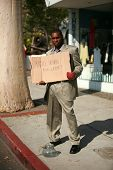 a thursty business man stands on a city street with a cardboard sign that reads