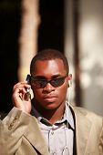 a well dressed african american man coducts business on his cell phone outside while listening on his personal digital music player