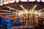Childrens Carousel At An Amusement Park In The Evening And Night Illumination. Amusement Park At Ni poster