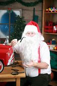 Santa Claus smokes his pipe as he takes a break from building toys for Christmas Presents around the world
