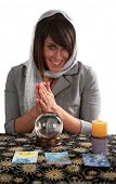 an attractive young fortune teller, looks into the future with her crystal ball, isolated on white,