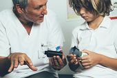 The Doctor Explains To A Young Diabetic Patient The Insertion System Of The Infusion Set Of An Insul poster