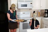 a mother and son enjoy peanut butter cookies in their kitchen while wearing gas masks in a post nucl