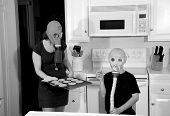 a mother and son enjoy hot fresh baked cookies in their kitchen while wearing gas masks in a post nu