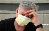 a man wears a yellow medical paper mask as he worries about how to stay safe from any air born illne