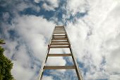 ladder to success, extention ladder extened into the blue sky with great white fluffy clouds. repres
