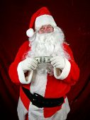 Santa Claus hold money in preparation to give to you for christmas or the concept of the high cost o
