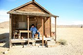 an old cowboy sits on the porch of his home after a hard day of gamblin' n drinkin' n chasin' saloon