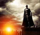 A Dark Heroic Costumed Superhero On A Rooftop Overlooking A Cityscape, Dramatic Sky, 3d Render, Mixe poster