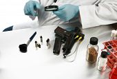 forensic analysis - a forensics lab technician examines a hand gun for finger prints, blood splatter