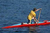 Jovem atleta em uma canoa a remo em frente