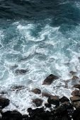 Foamy waves surfing on the rocky seashore