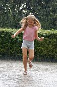 Young girl running in the heavy rain in the park