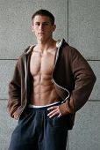 Young muscular man wearing a brown undone jacket