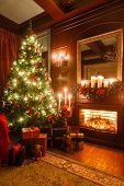 Gifts At The Christmas Tree. Christmas Evening By Candlelight. Classic Apartments With A Fireplace. poster