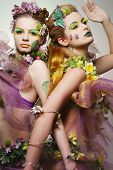 Portrait of two beautiful fashion models wearing costumes made of flowers.