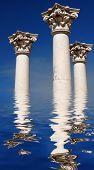 Três antigos grego pilares contra um céu azul refletindo na água