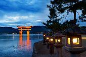 Great floating gate (O-Torii) on Miyajima island near Itsukushima shinto shrine, Japan shortly after the sunset with lit lanterns on the shore