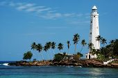 Beautiful white lighthouse Dondra Head, the southest cape of Sri Lanka - seen from the beach. The li