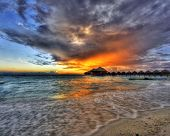 picture of sunset beach  - Beautiful vivid sunset over beach with the water villas in the Indian ocean - JPG