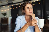 Thoughtful mature woman sitting in cafeteria holding coffee mug while looking away. Middle aged woma poster