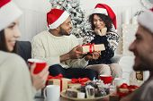 Happy African-american Girl Surprised While Her Boyfriend Giving Her Christmas Gift At Home Party, C poster