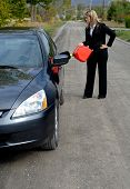Businesswoman Filling Her Car Up With Gasoline After Running Out Of Gas By The Side Of The Road