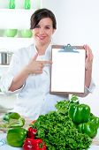Happy Chef Pointing To A Blank Clipboard In Her Kitchen With Copy Space For Your Message