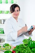 Woman Chef Making Notes On A Clipboard In Her Kitchen