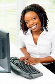 Beautiful Female African American Office Worker Sat At Her Computer Wearing A Telephone Headset
