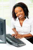 Trabalhador de escritório de americano Africano feminino bonito sentou-se ao seu computador usando um fone de ouvido do telefone