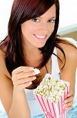 Pretty Young Woman Eating Popcorn While  Watching A Movie In Bed