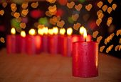Red Christmas candle burning on a wooden table, with a group of candles with hearts for flames on ba