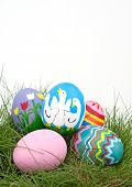 stock photo of duck egg blue  - An assortment of colorful hand painted Easter eggs on green spring grass - JPG