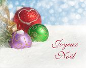Dreamy image of colorful Christmas ornaments in snow with text Joyeux Noel, Merry Christmas in Frenc